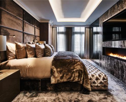 Metropolitan stijl slaapkamer, fluwelen boxspring in taupe met taupe hoofdbord, glanzende kussens en een inbouw-tv en sfeerhaard