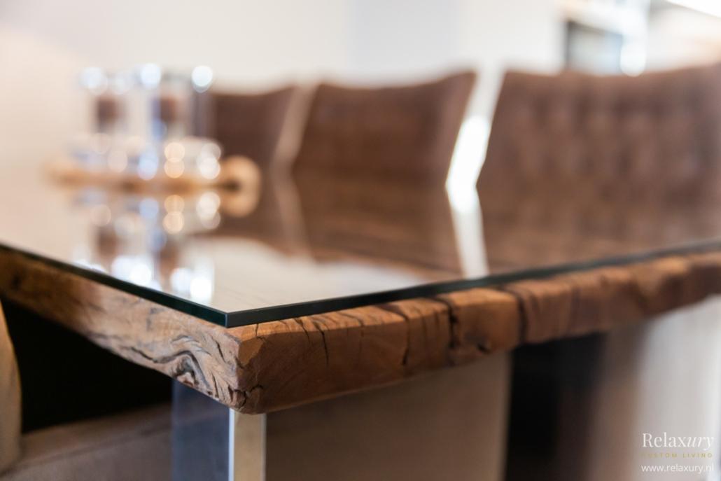 Houten tafel met glasplaat en metalen poten close-up
