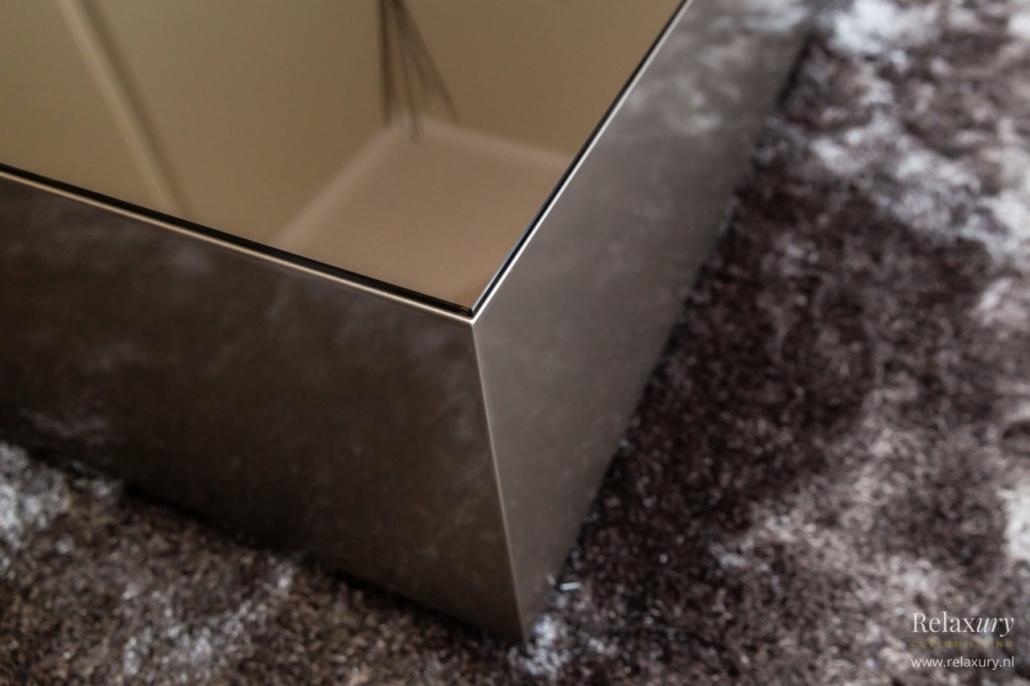 Bronzen bloktafel salontafel met glasplaat op bruin tapijt close-up