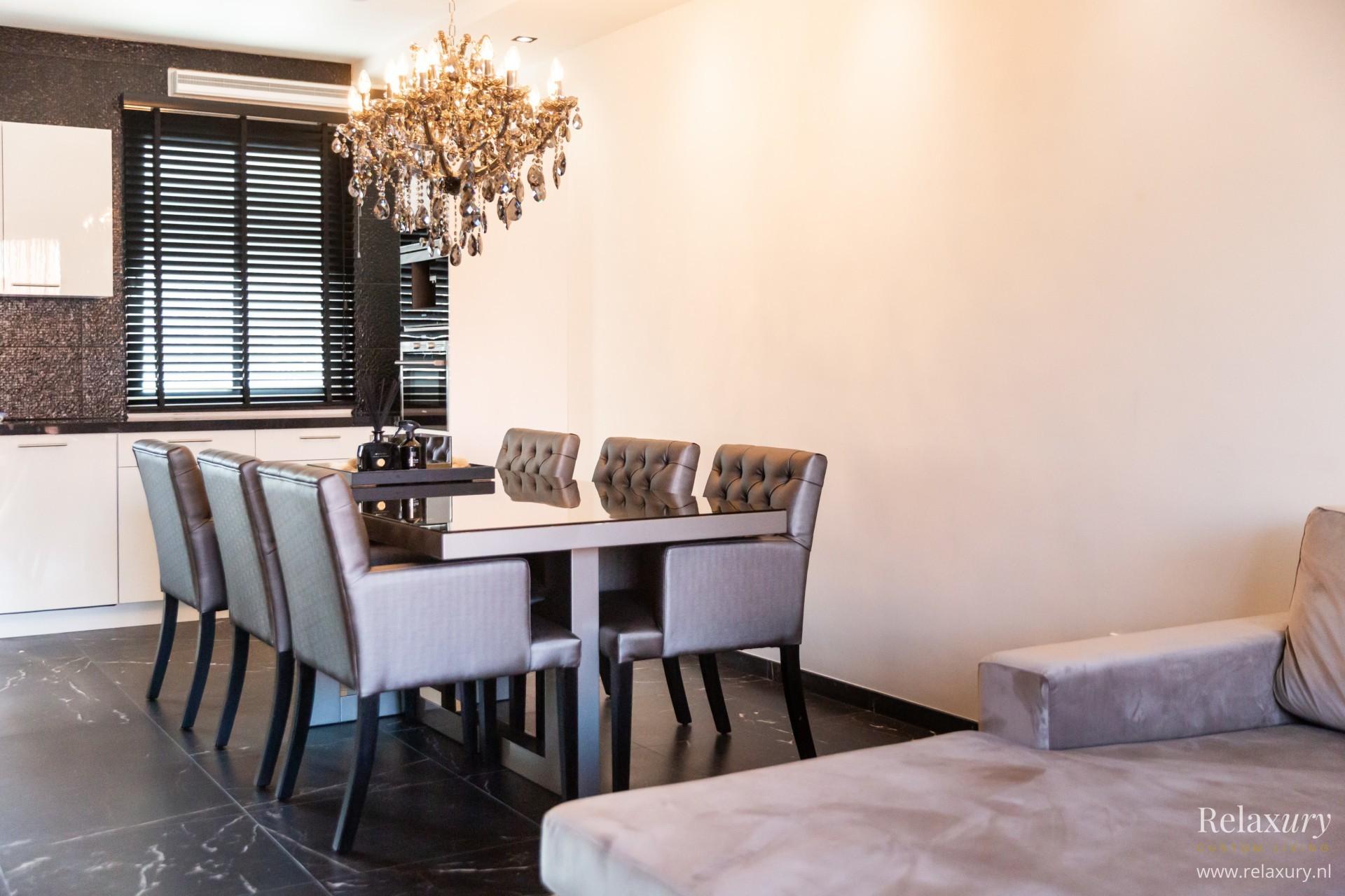 Hoogglans-eettafel-brons-glasplaat en bronzen gecapitonneerde eetkamerstoelen