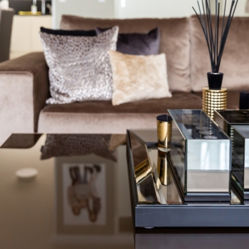 Glanzende bronzen bloktafel met wierookstokjes met bruine velours bank op de achtergrond