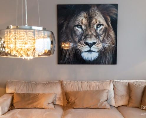 Lichtbruine velours bank met op de wand een foto van een leeuw en op de voorgrond een luxe kroonluchter