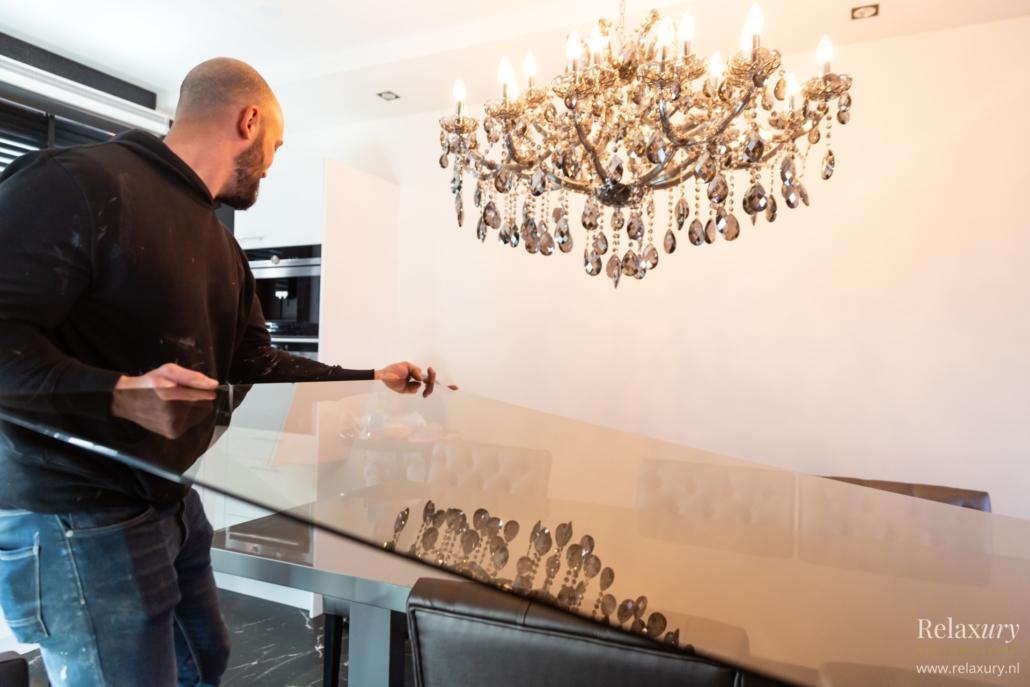 Relaxury eigenaar Emiel plaatst glasplaat op bronzen hoogglans eettafel