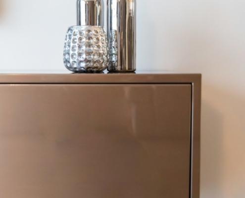 Zwevend tv-meubel brons luxury style close-up met zilverkleurig vaasje en zilveren wijnflessen